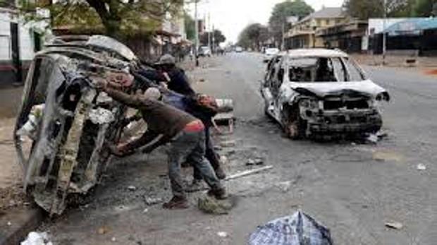 Recolectores de chatarra recuperan una carcasa de un automóvil quemado durante los ataques xenófobos en Johannesburgo, Sudáfrica.