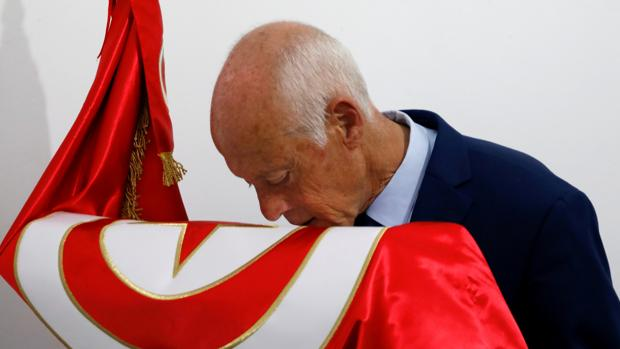 El candidato populista Kaïes Said besa la bandera tunecina tras conocer los resultados no oficiales que le asegurarían su pase a la segunda vuelta