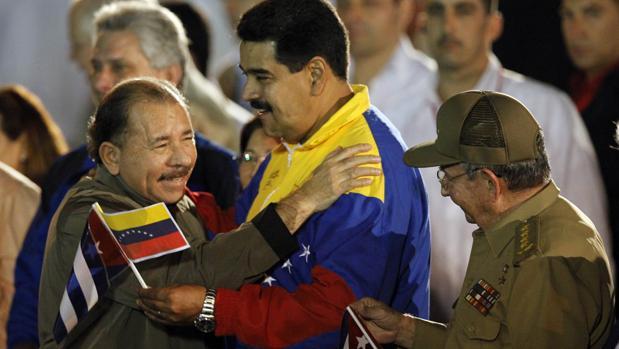 El presidente de Nicaragua, Daniel Ortega abraza a su homólogo venezolano, Nicolás Maduro, mientras el presidente de Cuba, Raúl Castro, observa a los dos líderes