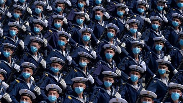 Un grupo de militares rusos desfilan durante un ensayo protegidos con mascarillas