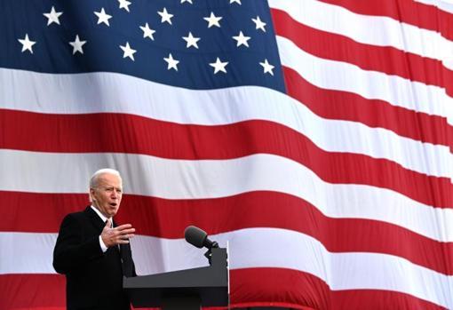 رئیس جمهور منتخب در مقابل پرچم بزرگ آمریکا طرفداران خود را خطاب قرار می دهد.