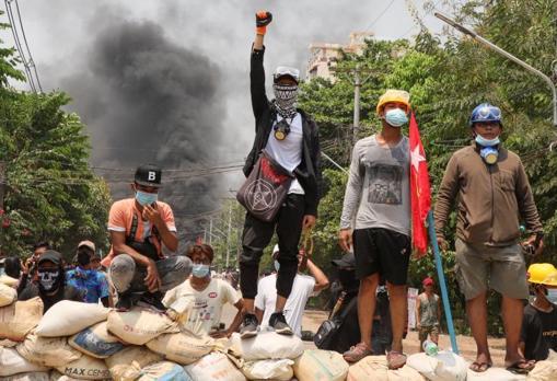 La gente se para en una barricada durante una protesta contra el golpe militar, en Yangon
