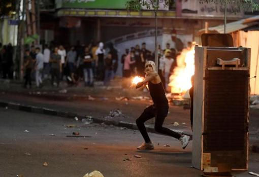 A young Palestinian prepares to throw a Molotov cocktail in Hebron (West Bank)