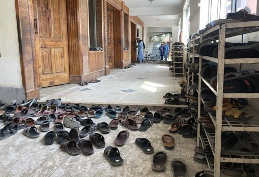 Lots of sandals at the entrance of a crowded class
