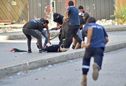 An injured person during the demonstration lies on the approach while several people help him