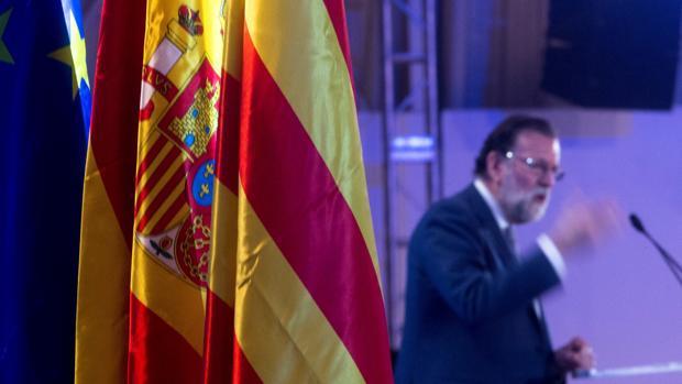 El presidente del Gobierno, Mariano Rajoy, junto a las banderas de la Unión Europea, de España y de Cataluña