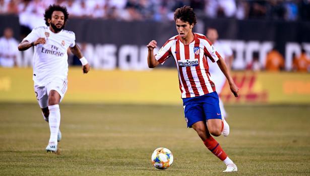 Marcelo, futbolista del Real Madrid (al fondo) intenta dar caza a Joao Félix, atacante del Atlético de Madrid