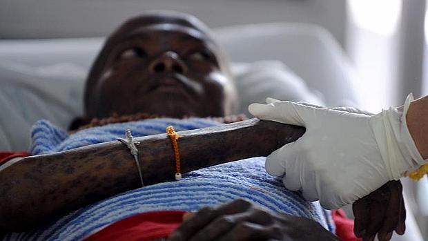 Un voluntario sujeta la mano de un infectado con el VIH