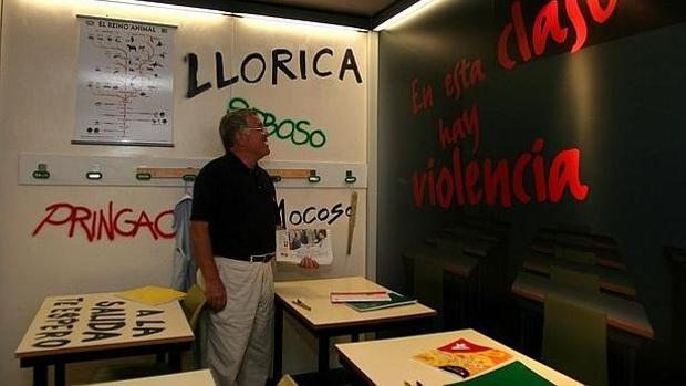 Un profesor contempla las pintadas en un aula en un caso de acoso escolar a un alumno