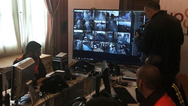 Unos operarios vigilan la zona de control de cámaras del Centro de Coordinación Operativa (CECOP) que coordina todo el dispositivo de seguridad de la Semana Santa de Sevilla