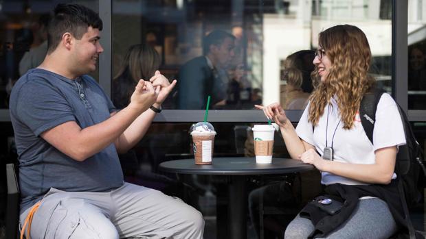 Dos jóvenes se expresan mediante lengua de signos en el local de Washington