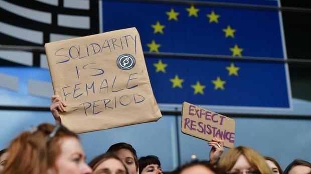 """Eurodiputadas del Parlamento Europeo y su personal sostienen una pancarta que dice """"Estamos en huelga"""" mientras protestan en la entrada principal del Parlamento Europeo para conmemorar el Día Internacional de la Mujer en Bruselas el 8 de marzo de 2019"""