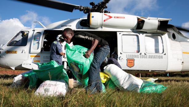 Varias personas bajan de un helicóptero sacos con ayuda humanitaria destinados a los afectados por el ciclón Idai, este viernes en Ngangu (Zimbabue)