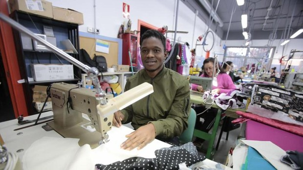 Un joven inmigrante trabaja en un taller de costura en Sevilla
