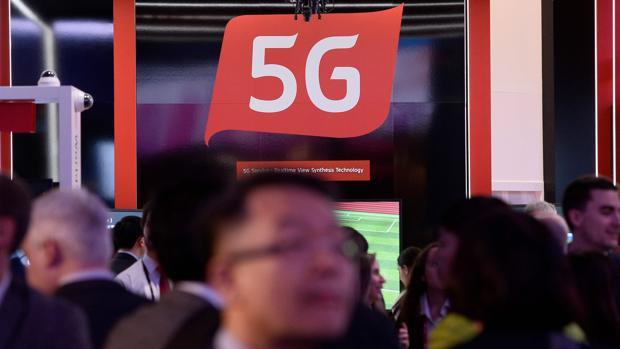 Personas pasan por un stand en donde se informa de las capacidades de las redes 5G