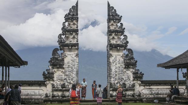 Turistas toman fotos del volcán Monte Agung que arroja ceniza volcánica caliente, visto desde el templo de Lempuyang