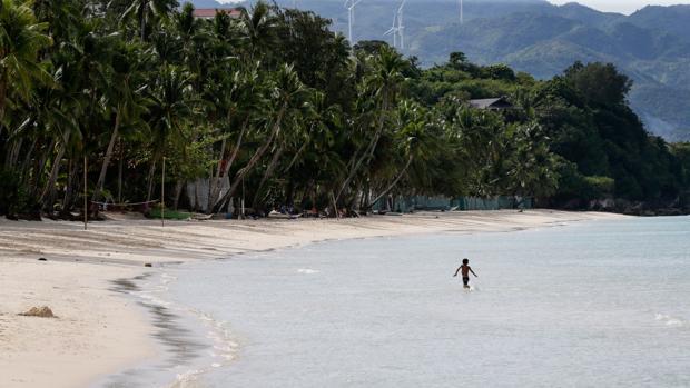 Un niño se baña en una de las playas de Boracay, abierta al público en modo de prueba