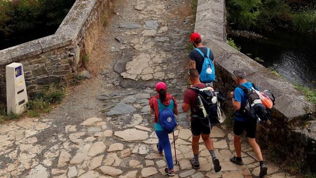 Varios peregrinos del Camino de Santiago cruzan el puente Romano de Furelos, en Melide (La Coruña), el pasado 1 de julio